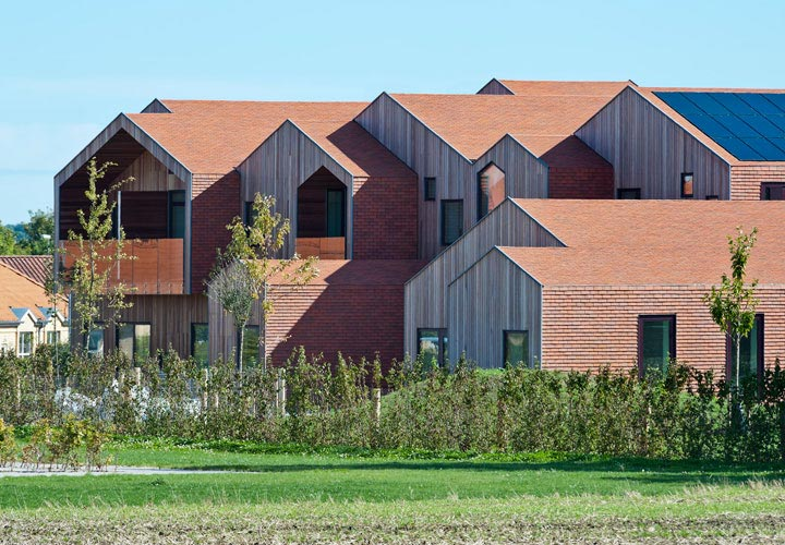 Children's Home of the Future building by CEBRA Architecture. Red tile cladded pitched roofs.