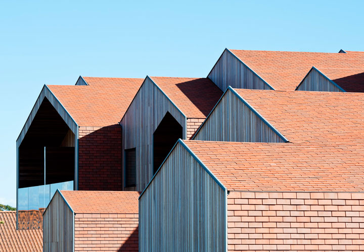 A series of shifting volumes and pitched roofs at the Children's Home of the Future building by CEBRA Architecture.