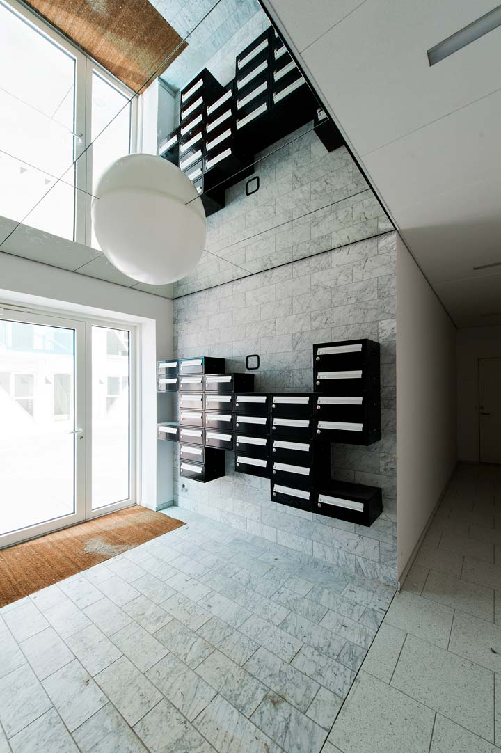 Inside the Iceberg Aarhus building by CEBRA architecture. Black and white mailboxes reflected in a mirror ceiling.