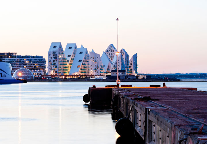 The Iceberg Aarhus building by CEBRA architecture seen from the harbor after sunset.
