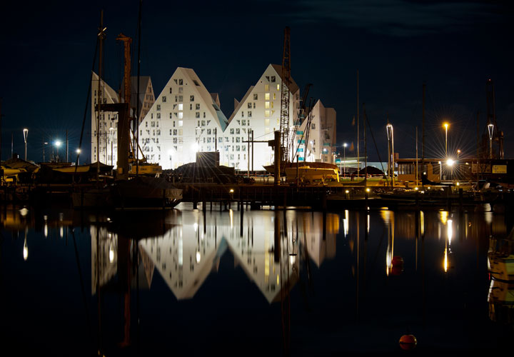 Nighttime picture of the Iceberg Aarhus building by CEBRA architecture. The white building is reflected in the water.