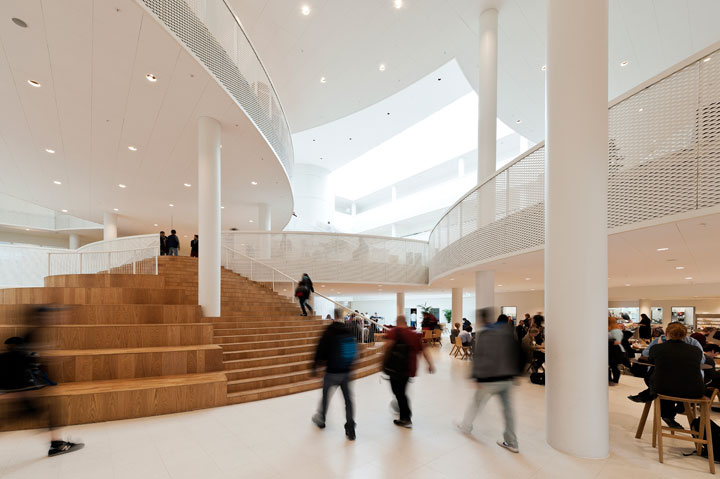 Many people walking inside the atrium of the HF & VUC Fyn. Some climb the central round staircase.