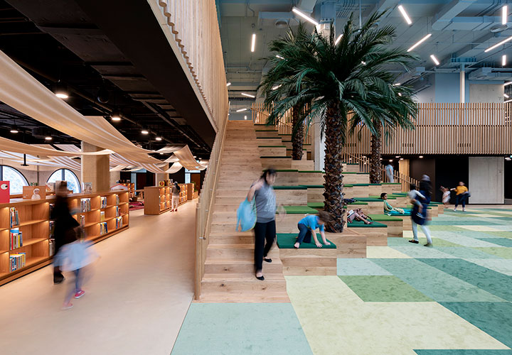 Children and parents at the big wooden staircase at the children's library in abu dhabi