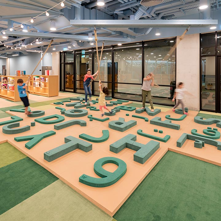 Kids playing on top of oversized letters of the alfabet and numbers at the children's library in abu dhabi