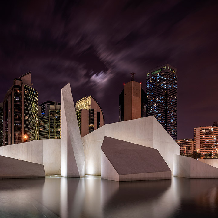 Nighttime view of the Al Musallah prayer hall in Abu Dhabi designed by CEBRA Architecture reflected at a water feature