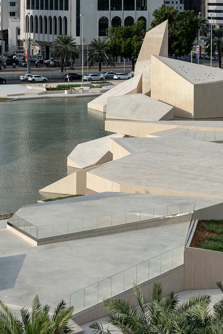 Daytime view of the Al Musallah prayer hall in Abu Dhabi designed by CEBRA Architecture reflected at a water feature