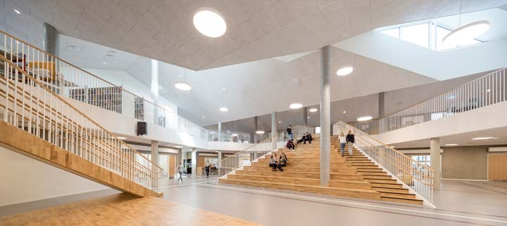Interior gathering space at Skovbakke School. Wood staircase invites to climb first floor.