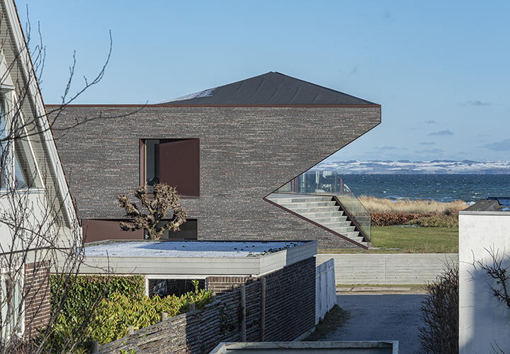 the brick facades enclose the central living space to ensure privacy while opening towards the water with the hilly Mols peninsulas visible on the opposite side of the bay