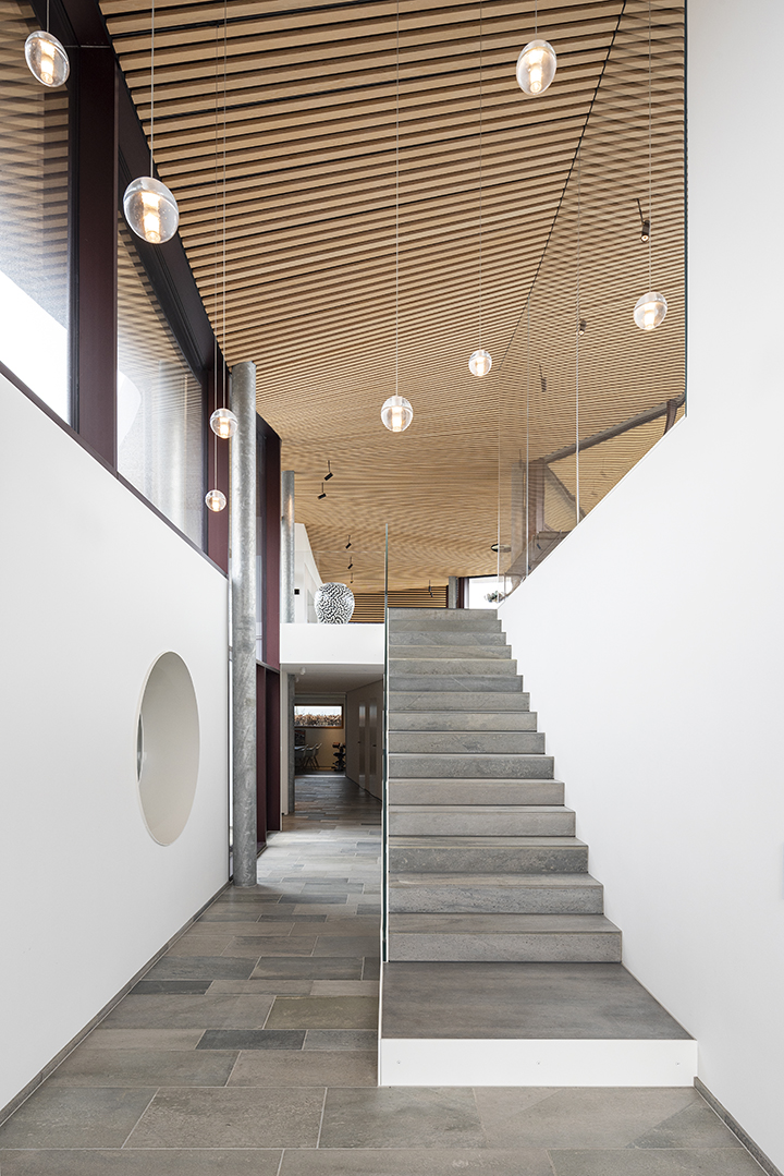 the lower level forms a base of ancillary functions from where a staircase leads up to the heart of the seaside villa