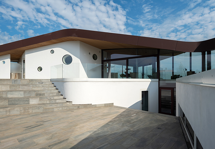 backyard view of the seaside villa from the lowered terrace that creates a protected outdoor space between the two floors