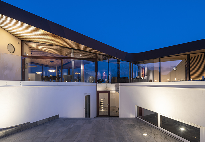 evening view from the backyard highlighting the transparent living space under the curving roof