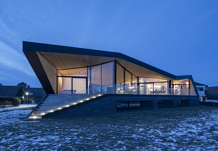 evening view from the seaside highlighting the transparent living space under the curving roof
