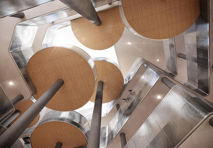 Interior view of the Aarhus Vand headquarters' atrium space from the ground floor looking upwards between the circular platforms on columns in shifting locations across the floors